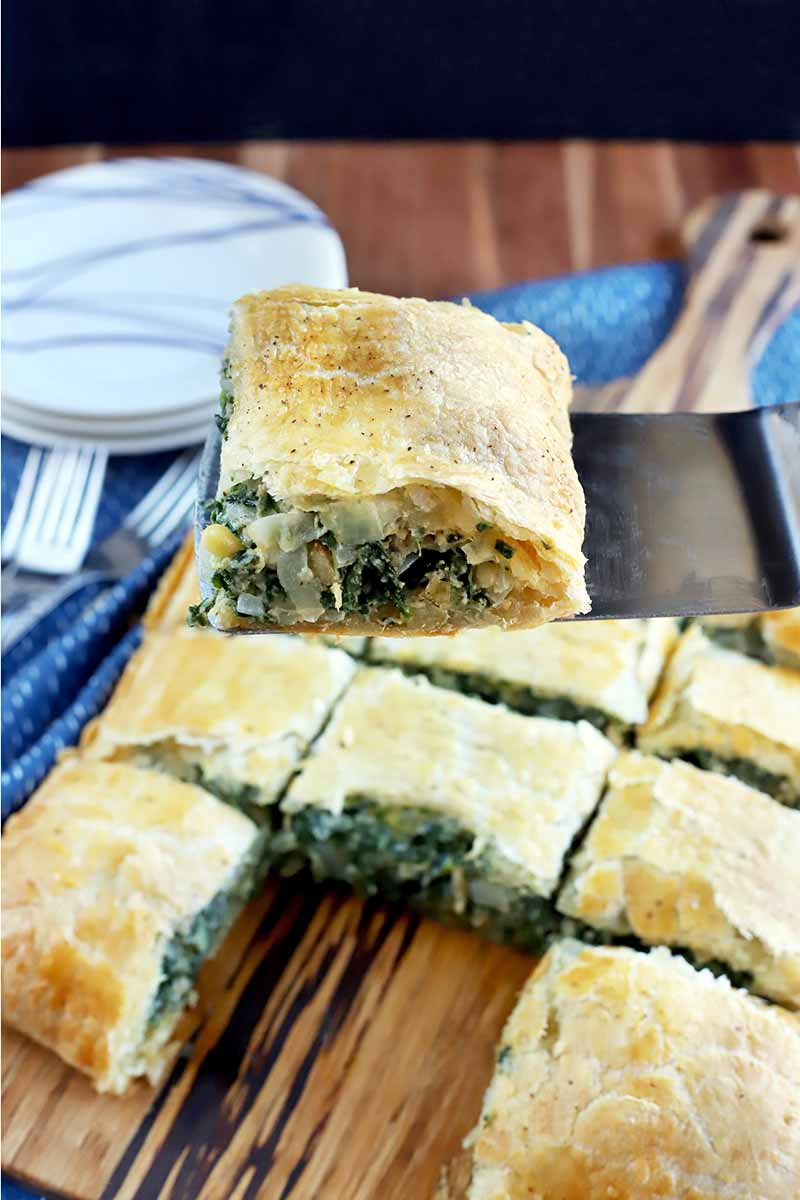 A metal spatula holds a slice of spinach in puff pastry up to the viewer, with more pieces arranged in rows on a wood board in the background, on a blue cloth on top of a wood surface, with a small stack of plates and forks to the left, on a black background.