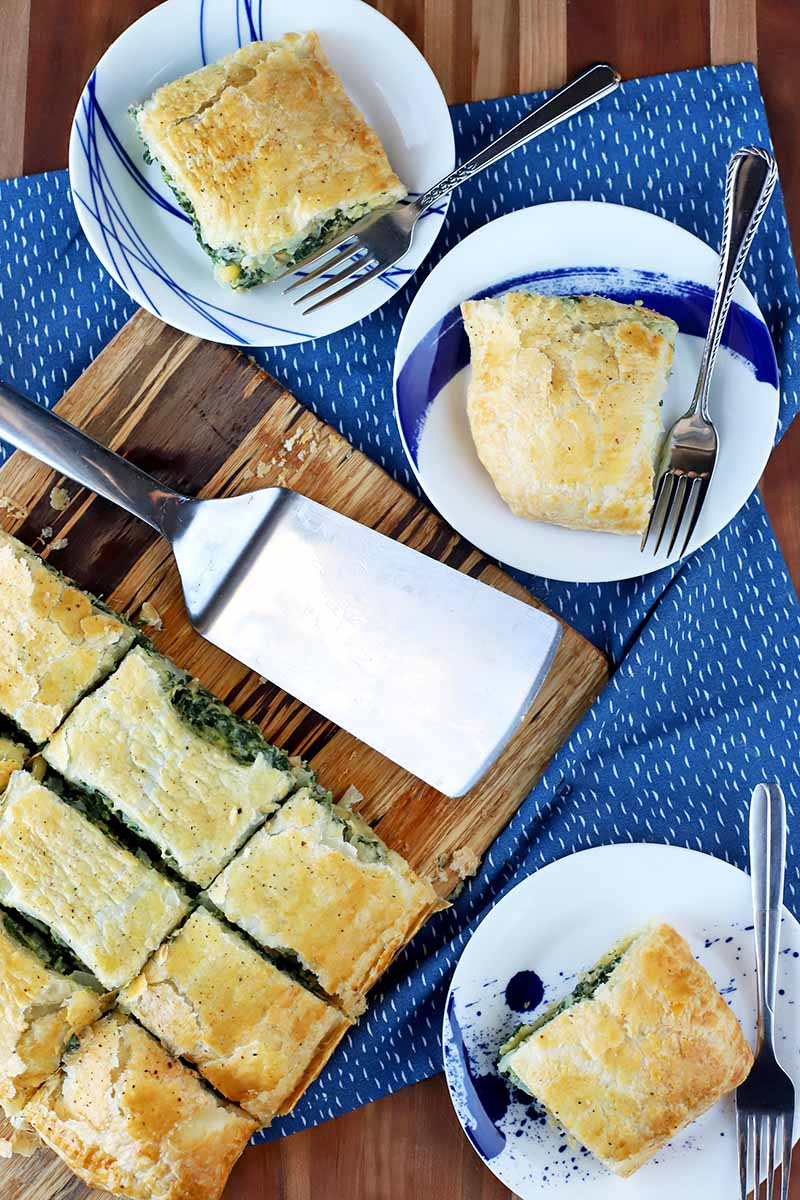 Overhead shot of three small plates of sliced spinach in puff pastry with more on a wood board with a metal spatula to the left, with forks on each plate, on top of a blue cloth with white flecks, on a wood surface.