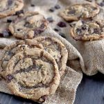 A cluster of three homemade vegan cookies is in the foreground with four more in the background among scattered chocolate chunks on a folded and gathered piece of burlap spread over a dark brown wood surface.