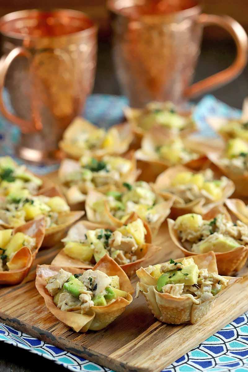 Wonton cups filled with a tropical chicken mixture and topped with a sprinkling of fresh herbs are arranged on a wood serving platter, on top of a dark and light blue cloth on a dark brown wood surface, with two copper Moscow Mule mugs in soft focus in the background.
