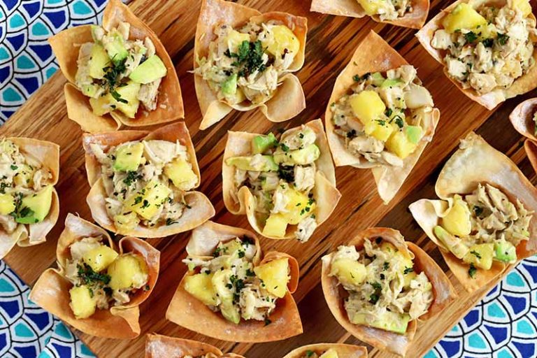 Overhead shot of tropical chicken cup appetizers on a wood board, on top of a dark and light blue patterned cloth.