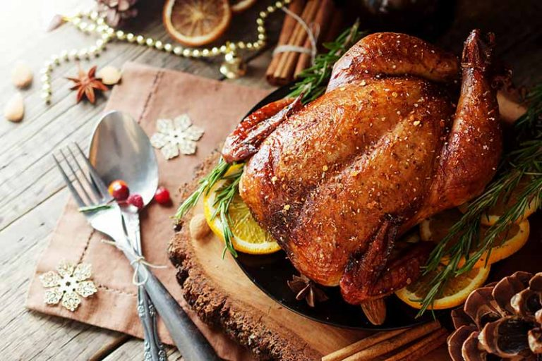 Horizontal close-up image of a roast turkey with citrus, herbs, and other assorted decorations.