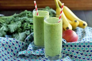 Two tall glasses filled with a green smoothie with red and white striped straws are at the center of the frame, surrounded by kale, bananas, and apples on a dark and light blue patterned cloth, on a dark brown surface with a lighter brown background.