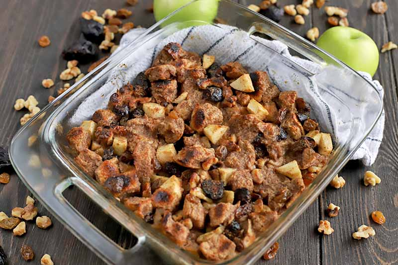 A square glass baking dish with handle cutouts on either side is filled with whole wheat bread pudding, on top of a white cloth kitchen towel with scattered walnut pieces, raisins, dried figs, and two green apples, on a dark brown wood surface.