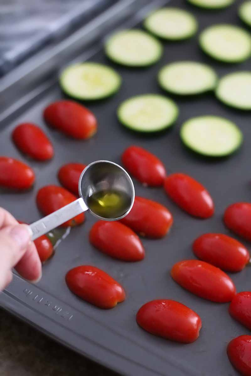 A hand drizzles a metal teaspoon measure of olive oil onto sliced zucchini and grape tomatoes on a baking sheet in soft focus in the background.