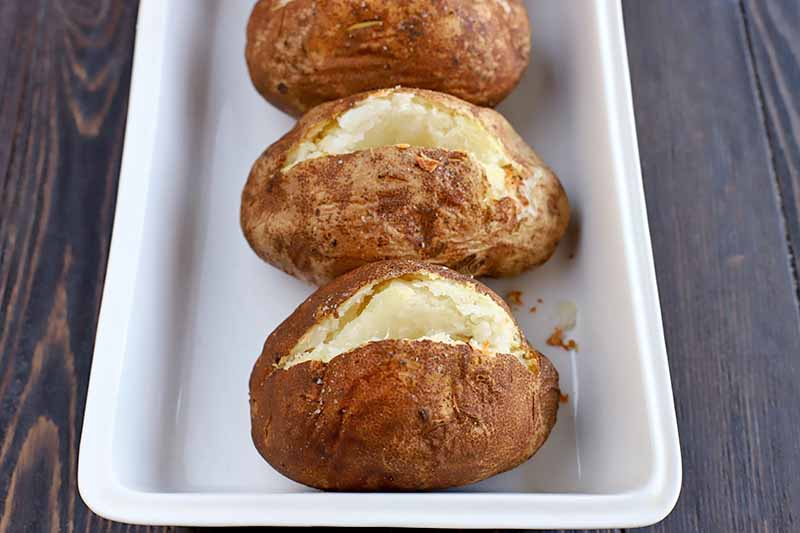 Three baked potatoes that have been cut open on top, arranged in a white rectangular ceramic baking dish, on a dark brown wood surface.