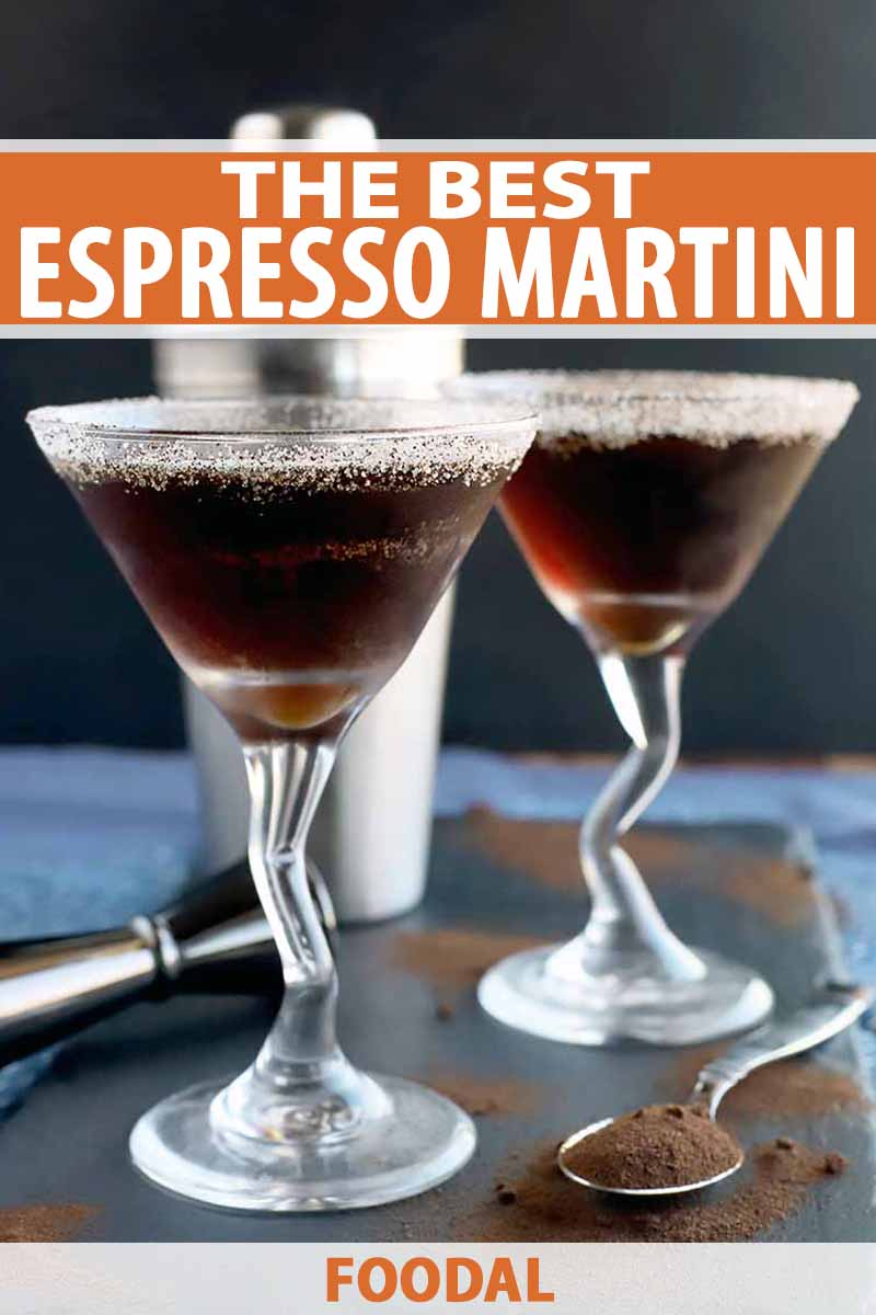 Vertical image of two espresso martinis on a slate serving platter with a stainless steel cocktail shaker and jigger, and a spoonful of coffee powder with more scattered on the surface, on a blue and white cloth with a charcoal gray background, printed with orange and white text.