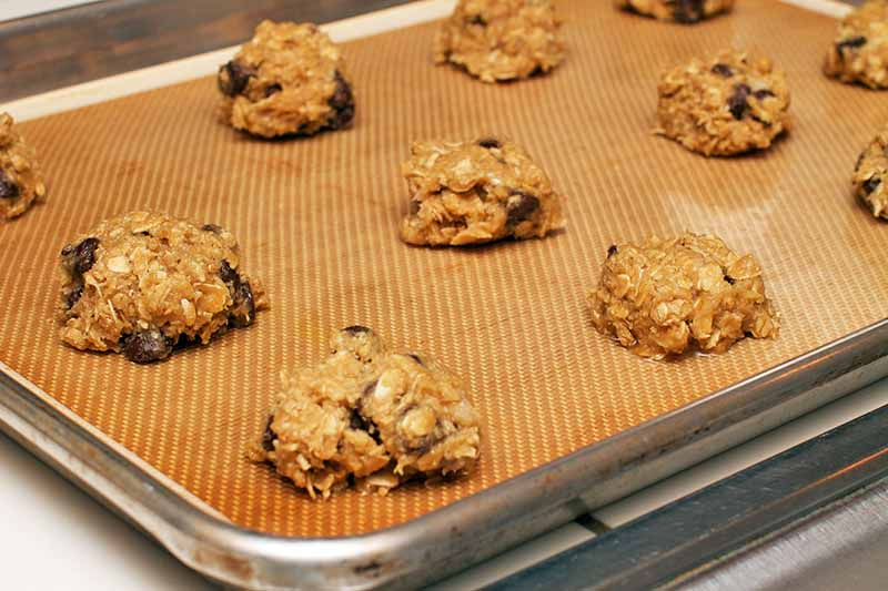 Closely cropped horizontal image of oatmeal raisin cookie dough portioned on a silicone pan liner set into a sheet pan.