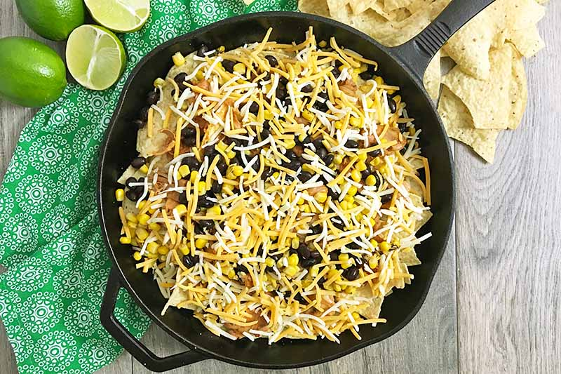 Horizontal image of cheese and other toppings on top of chips in a skillet.