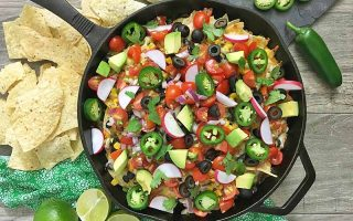 Horizontal image of a cast iron skillet with various nacho toppings next to chips on a green napkin