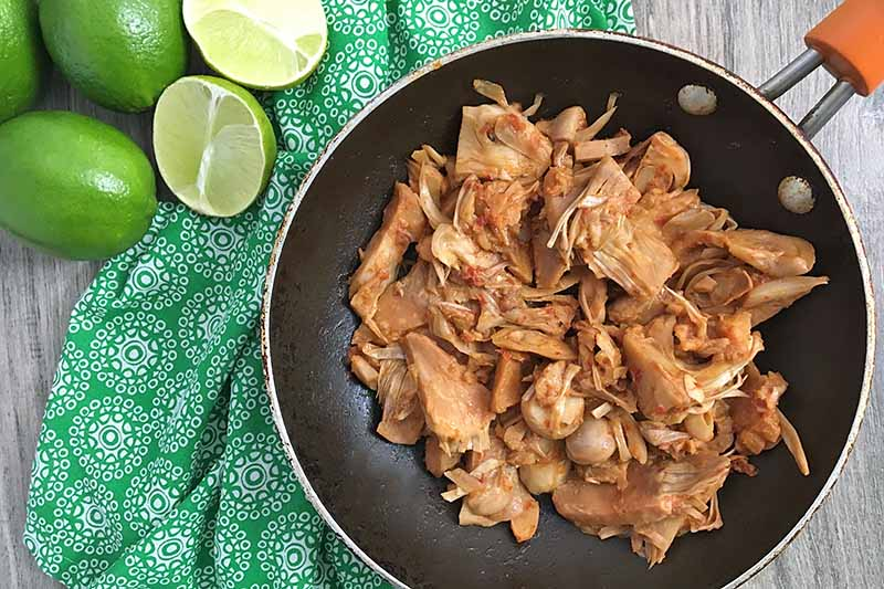 Horizontal image of sauteed jackfruit chunks in a skillet on a green napkin next to limes.