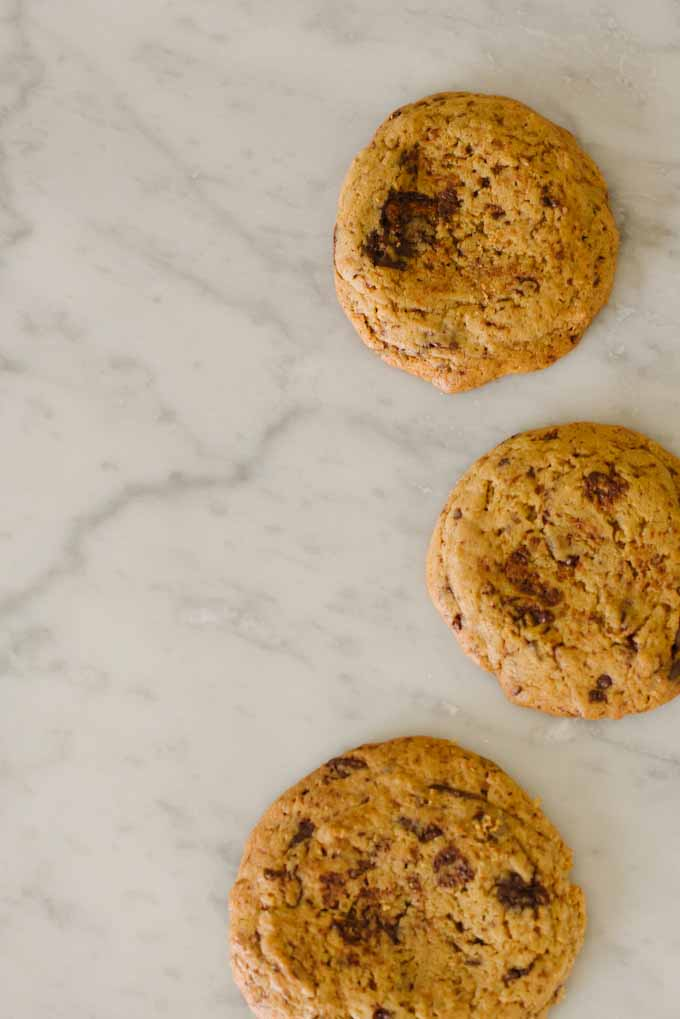 Top down view of three einkorn chocolate chip cookies on a marble kitchen countertop.