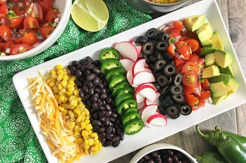 Horizontal image of assorted toppings on a white plate on a green napkin surrounded by other toppings in bowls.