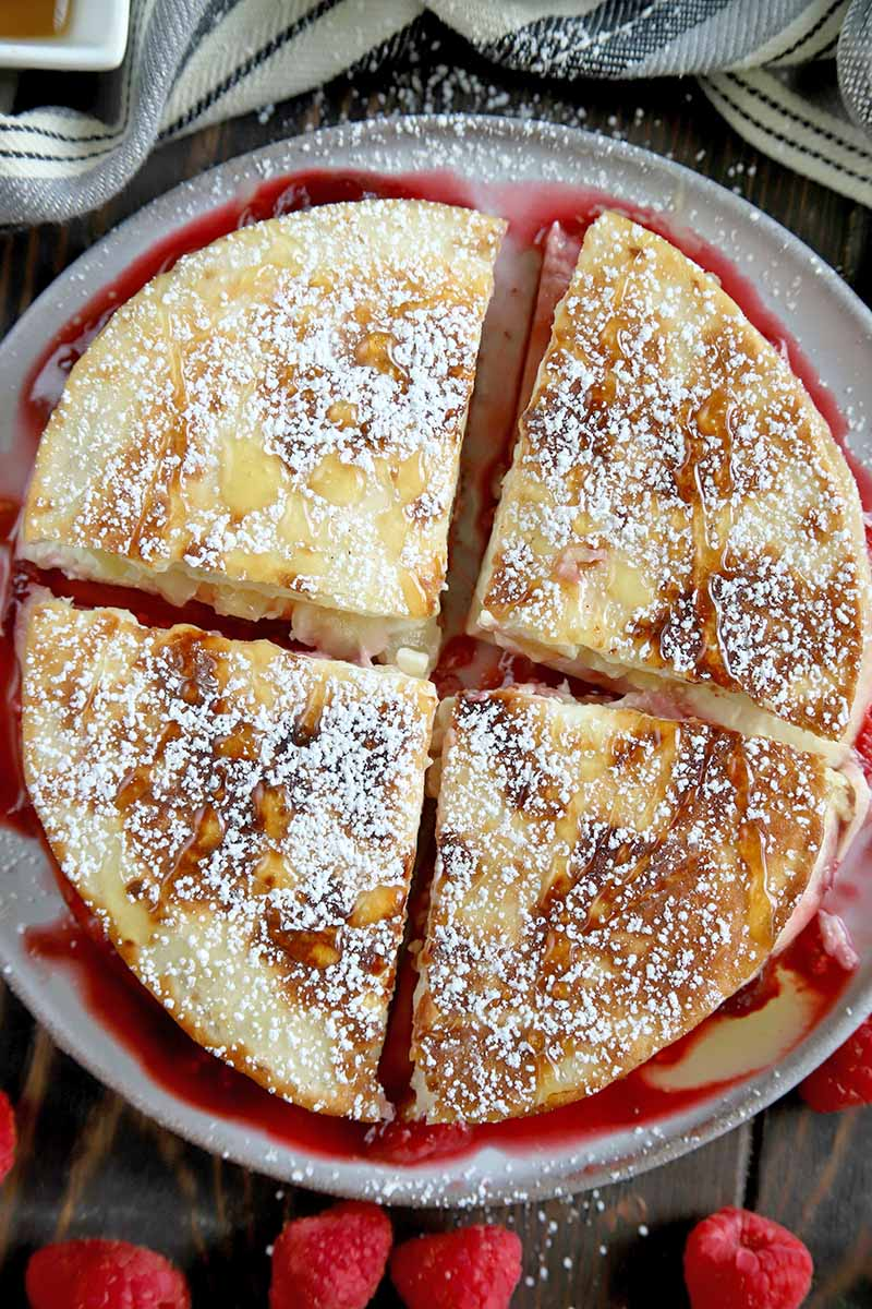 Vertical overhead image of a cream cheese and fruit quesadilla topped with powdered sugar and cut into four pieces, on a white plate on top of a brown wood surface with scattered red raspberries.