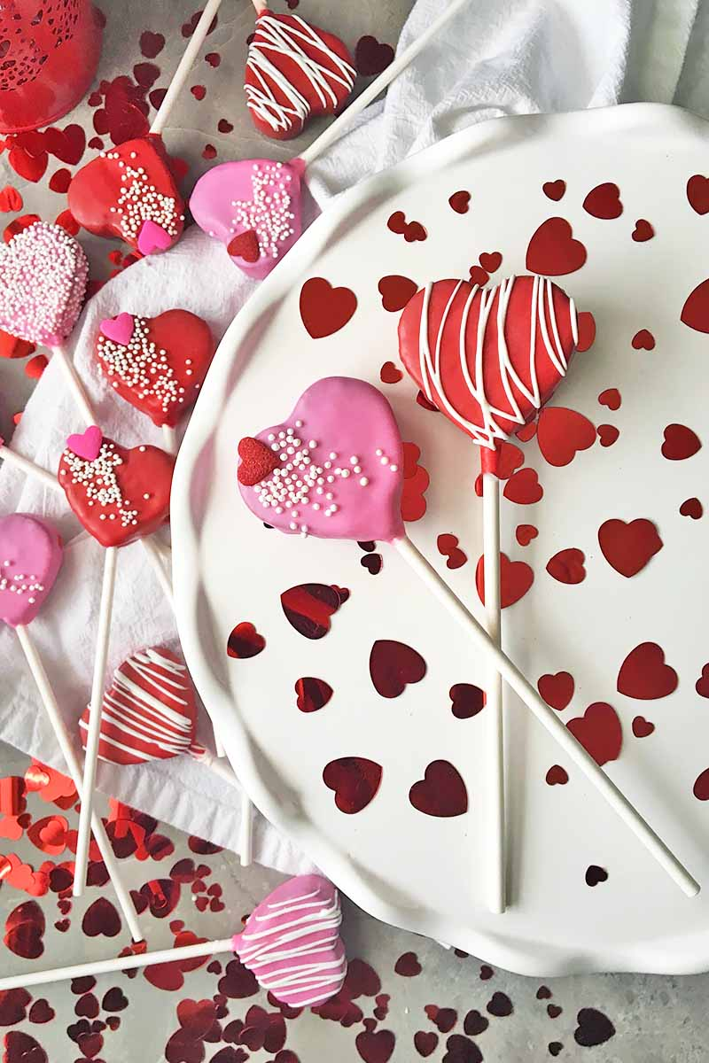 Vertical top-down image of assorted pink and red heart-shaped mini desserts scattered throughout the image.