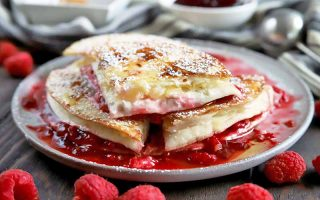 Horizontal oblique head-on image of four pieces of a dessert quesadilla made with fruit and cream cheese and garnished with powdered sugar arranged on a white plate, with small dishes of filling ingredients in the background and red raspberries scattered in the foreground, on a brown wood table.