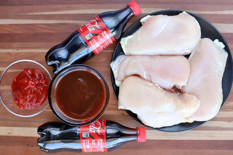 Overhead shot of two small bottles of Coca-Cola, a black plate with four uncooked boneless, skinless chicken breasts, and two glass bowls of ketchup and barbecue sauce.