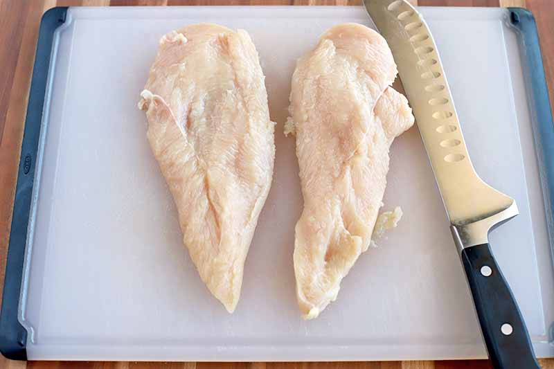 A chicken breast cut in half and arranged on a white plastic cutting board with a serrated knife with a black handle, on a wood surface.