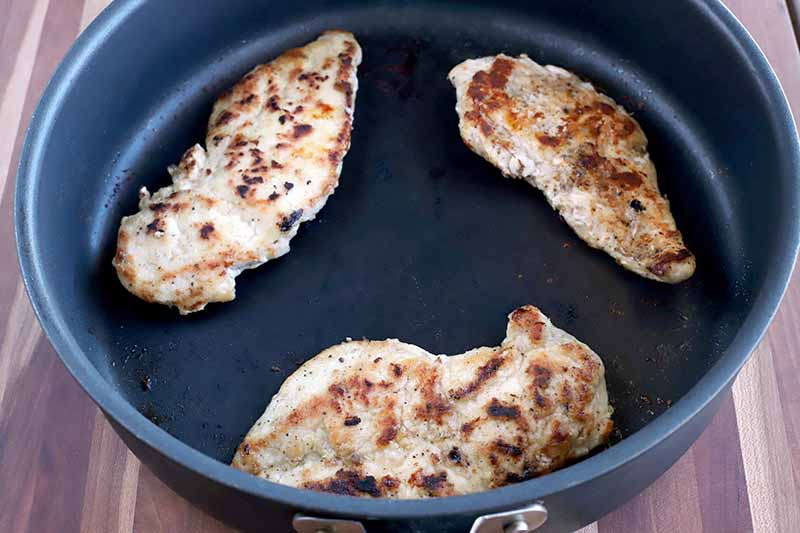 Three pieces of browned chicken breast in a nonstick frying pan on a wood surface.