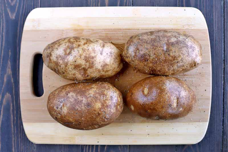 Four russet potatoes on a wooden cutting board, on a dark brown wood surface.