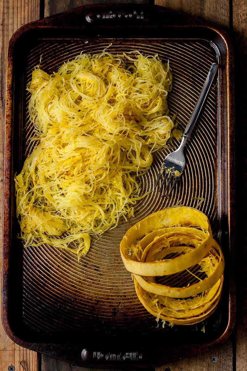 Vertical image of the cooked interior of spaghetti squash and its skin and a fork on a sheet pan.