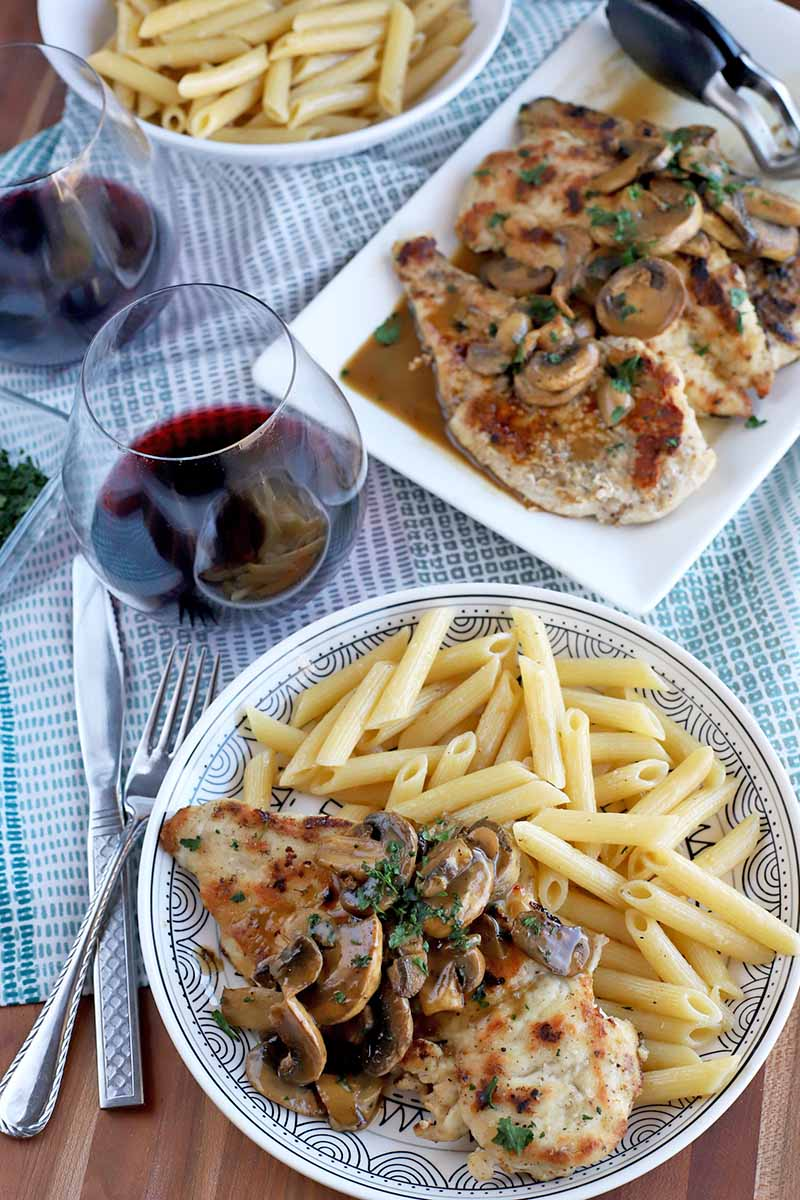 Vertical overhead shot of a plate of chicken marsala with penne pasta, with serving platters of more protein and macaroni, two stemless glasses of red wine, and a fork and a knife, on a light blue and white cloth, on top of a brown wood surface.