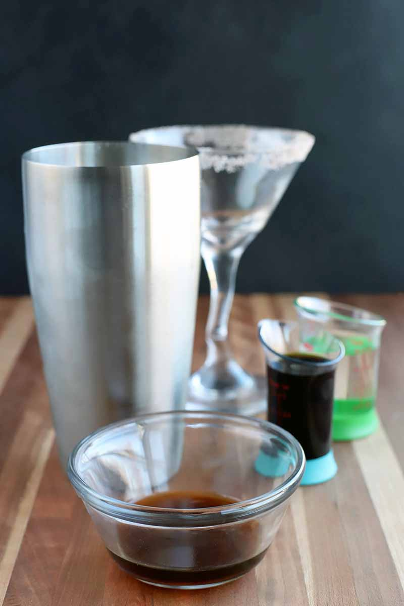 Vertical image of a cocktail shaker, a martini glass, a small glass bowl of coffee liqueur, and beaker-style shot glasses of vodka and espresso, on a wood surface with a charcoal gray background.