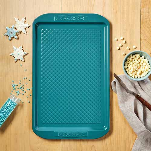 Overhead square image of an aqua ceramic-coated Farberware rimmed sheet pan with a textured surface, on a wood table with Christmas cookies, sprinkles, and a gray cloth.