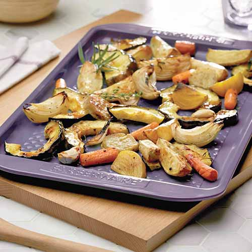 Square closely cropped image of a lavender rimmed Farberware baking pan of roasted vegetables, on a wooden cutting board on a countertop.