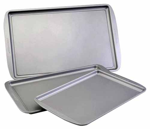 Three silver-colored Farberware rimmed baking pans in small, medium, and large sizes, isolated on a white background.