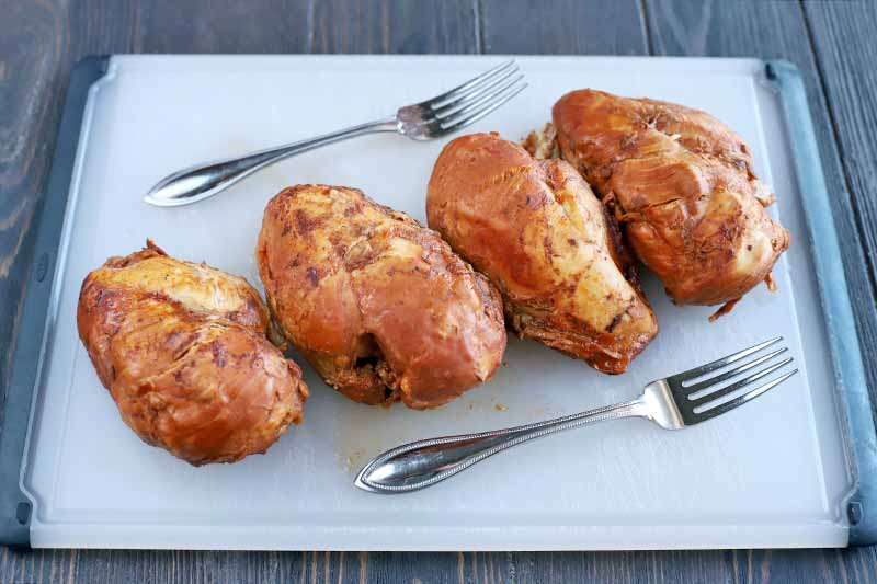 Four cooked chicken breasts in barbecue sauce are arranged at a diagonal on a white plastic cutting board with black rubber edging on the two short sides, and two forks arranged on either side of the meat, on a dark brown wood surface.