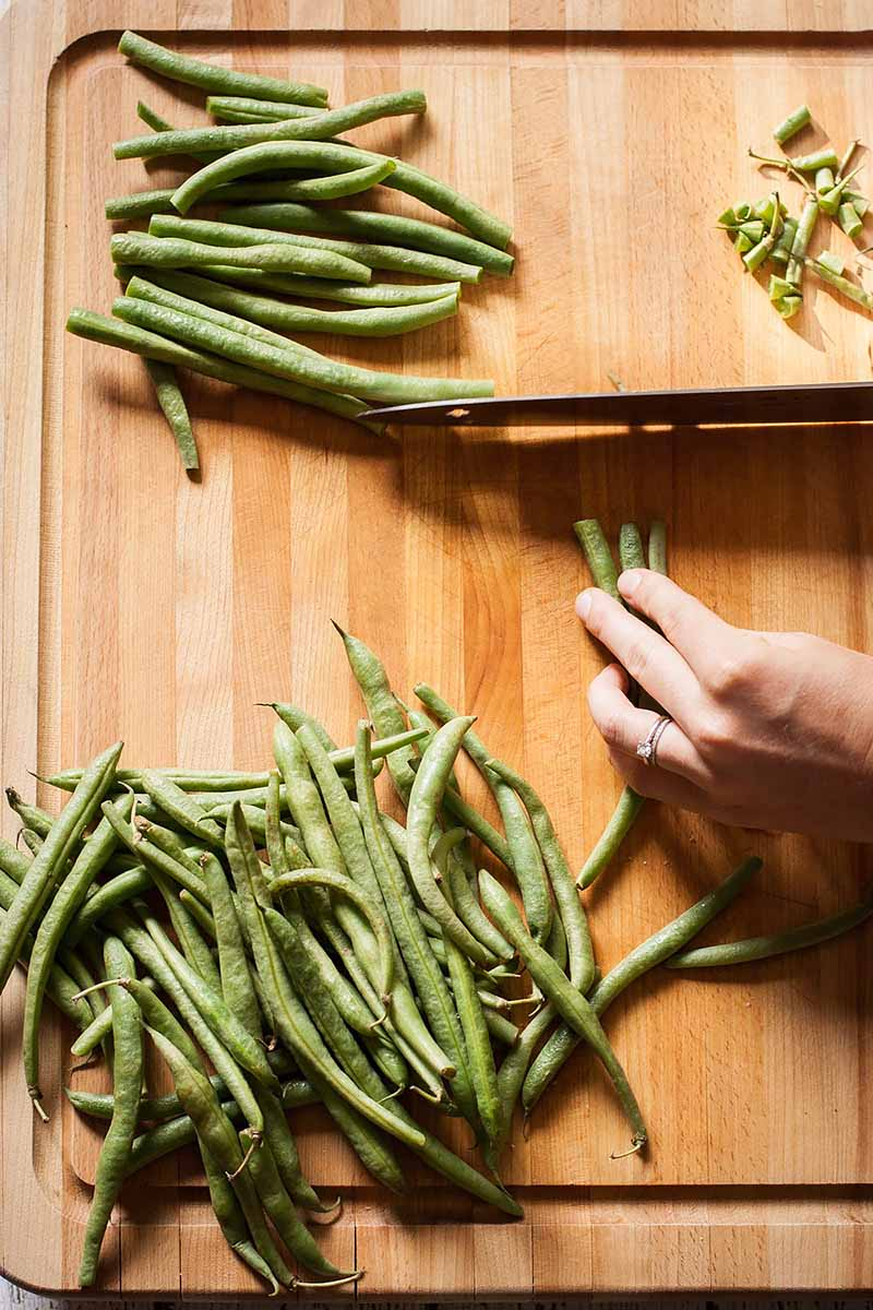 Vertical image of hands prepping fresh green beans on a wooden cutting board.