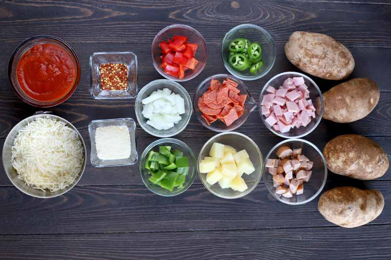 Overhead shot of ten glass bowls of three different sizes and two square glass bowls filled with shredded mozzarella, marinara sauce, grated Parmesan, red pepper flakes, chopped onion, tomato, jalapeno, green bell pepper, pineapple, pepperoni, ham, and sausage, with four baking potatoes to the right, on a dark brown wood table.