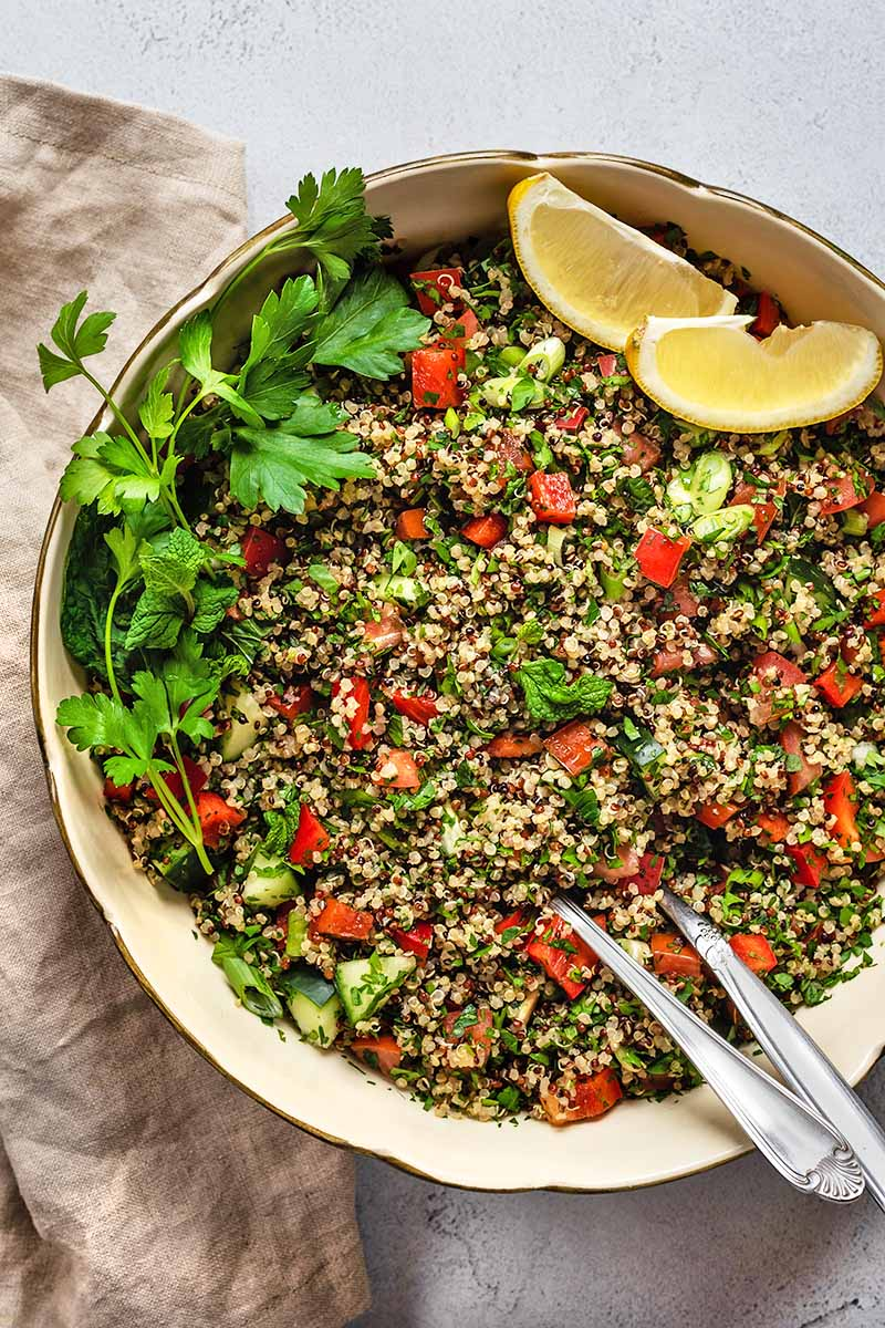 Overhead closely cropped shot of a large ceramic serving bowl of quinoa tabbouleh with two metal serving utensils, two wedges of lemon, and sprigs of fresh parsley, on a folded beige cloth, on a white and gray speckled surface.