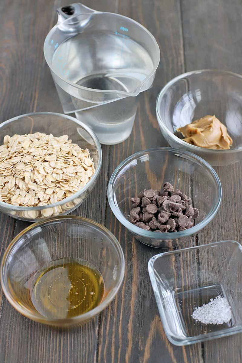 Four round glass bowls and one square glass bowl of quick-cooking oats, honey, dark chocolate chips, creamy peanut butter, and salt, with a plastic measuring pitcher of water in the background, on a dark brown wood surface.