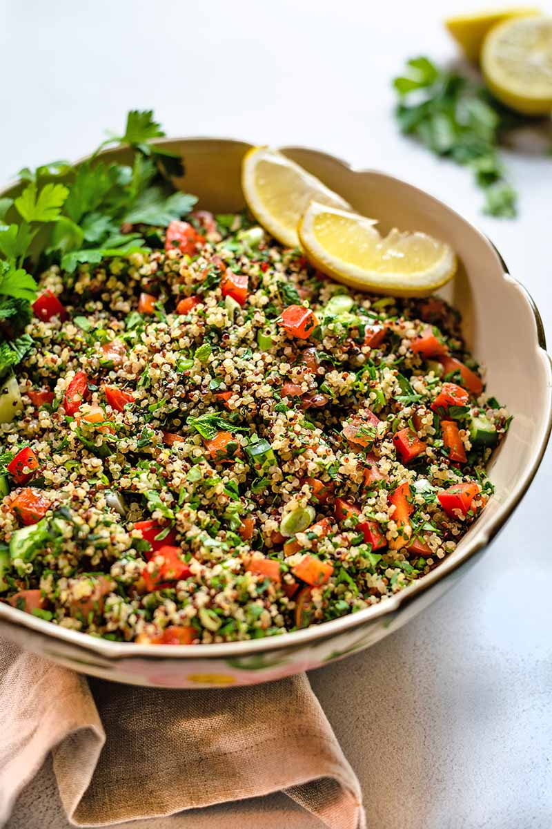Closely cropped oblique vertical shot of a large, beige, ceramic serving bowl of quinoa tabbouleh with fresh herbs and lemon, on a folded beige cloth on a white and gray speckled surface, with more citrus and herbs in soft focus in the background.