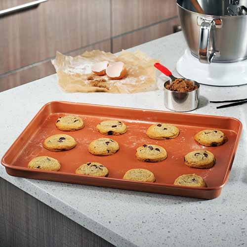 Square image of twelve cookies in three rows on a copper-colored Gotham Steel rimmed baking sheet, on a gray kitchen counter with baking ingredients, a mixer, and measuring implements.