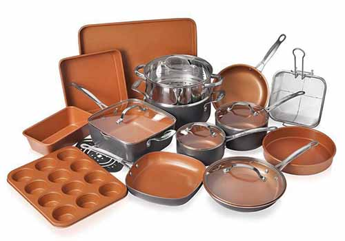Twenty-piece Gotham steel cookware and bakeware set with copper colored pans, isolated on a white background.