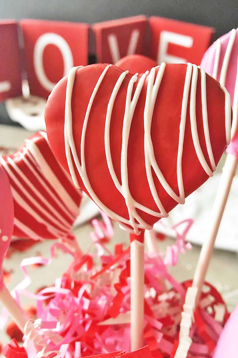 Vertical close-up image of a red heart-shaped cake pop.