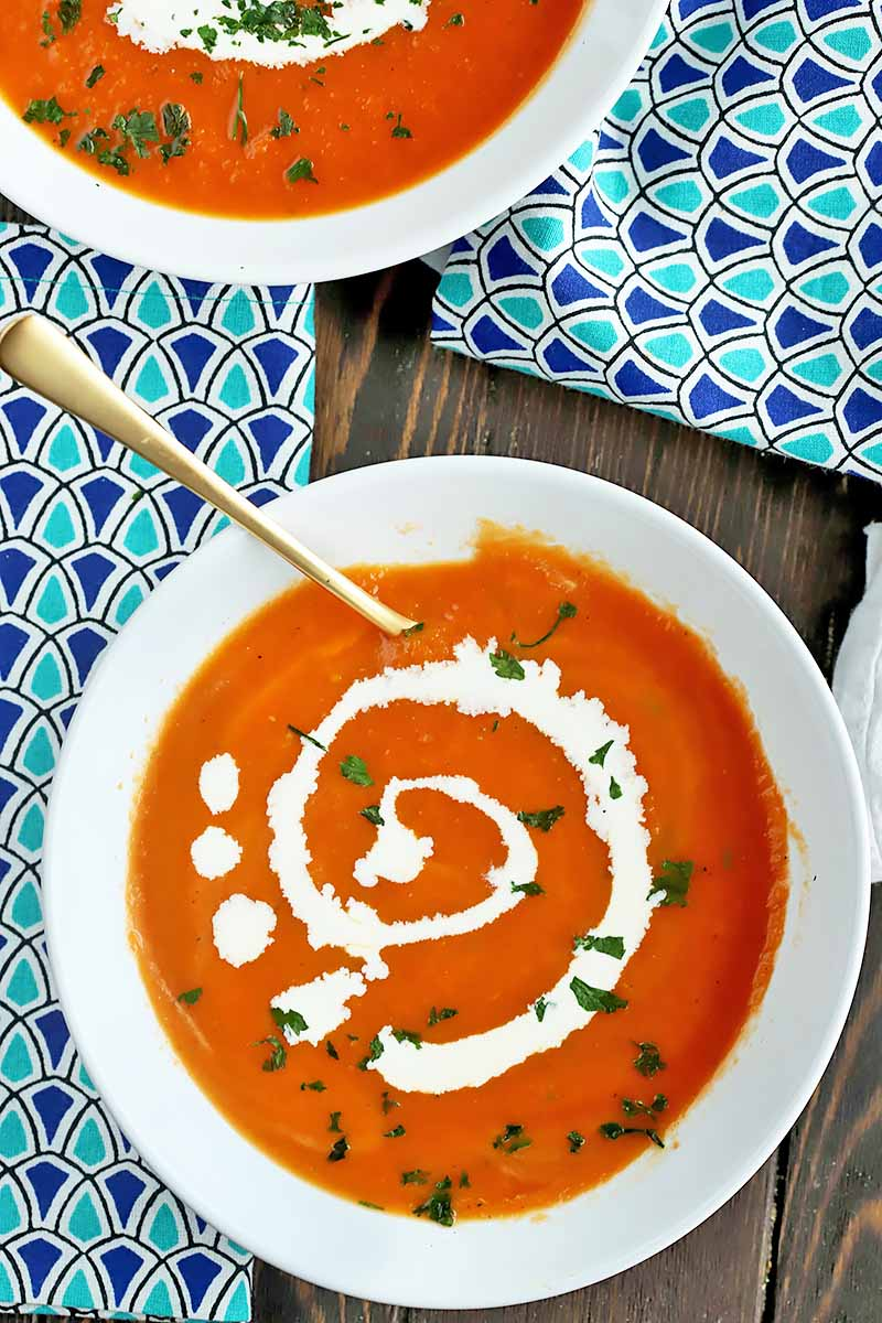 Vertical top-down image of a white bowl with orange liquid and garnishes and a spoon.
