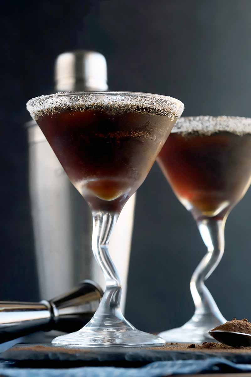 Two espresso martinis with sugar rims in glasses with decoratively bent stems, on a slate surface with a stainless steel cocktail shaker and a measuring jibber, on a blue cloth, with a charcoal gray background.