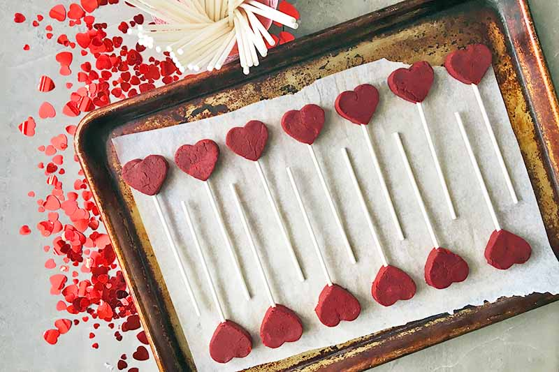 Horizontal image of heart treats inserted with white sticks on a sheet pan.