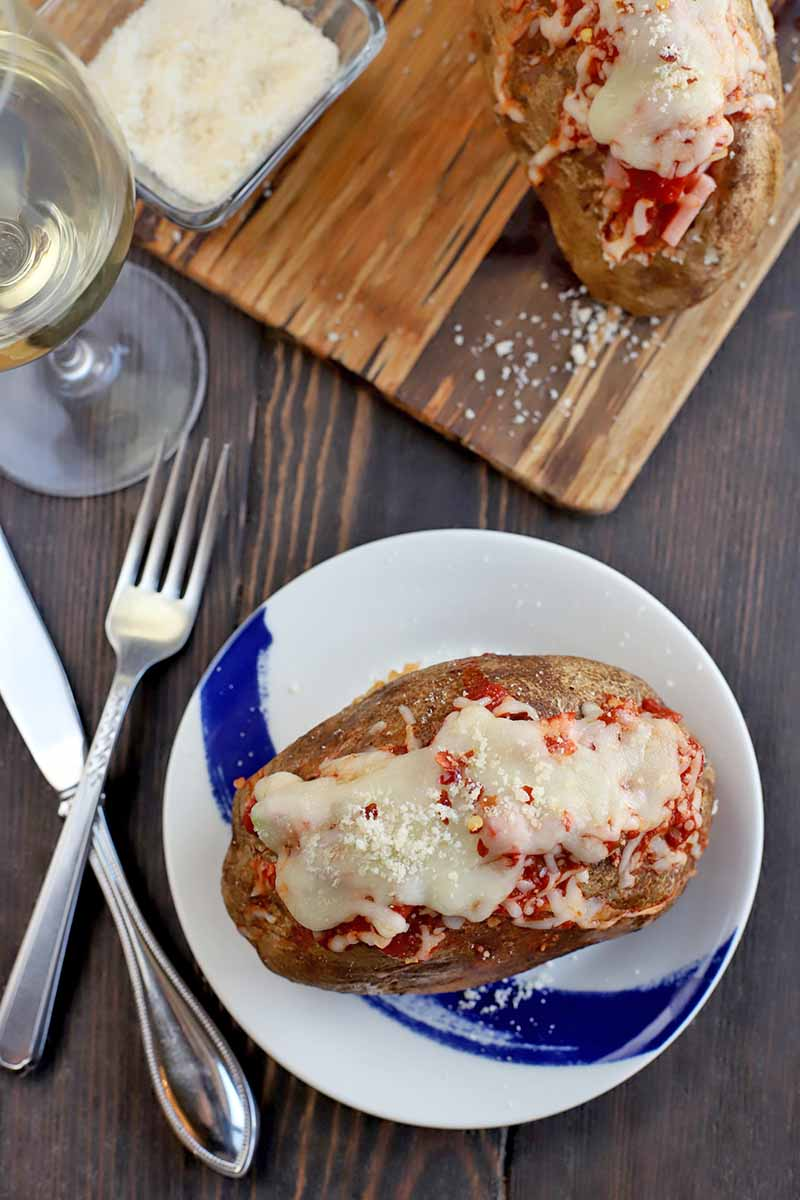 Overhead shot of a baked potato with pizza fillings on a blue and white plate, with a crossed knife and fork to the left, a glass of white wine, and a serving board topped with more spuds, and a small, square, glass dish of grated Parmesan, on a dark brown wood surface.