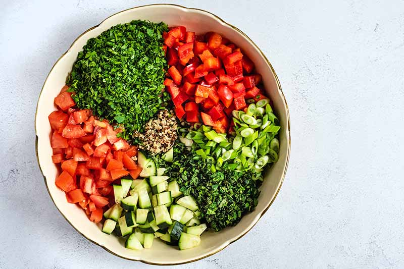 Overhead shot of a large ceramic bowl filled with unmixed portions of chopped parsley, tomatoes, scallions, mint, cucumber, and bell pepper, on top of cooked multicolored quinoa, on a white and gray speckled surface.