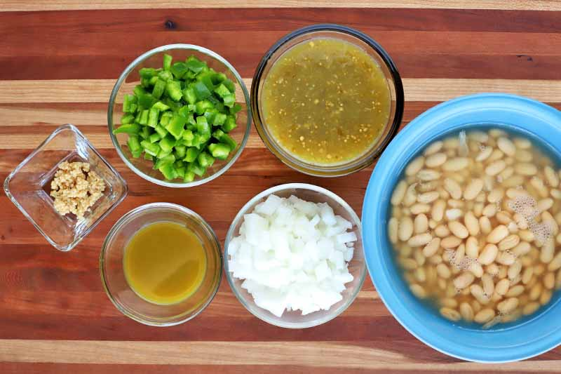 Overhead shot of a square glass bowl of minced garlic, round glass bowls of chopped green bell pepper, onion, jalapeno hot sauce, and salsa verde, and a blue bowl of canned cannellini beans in their liquid, on a striped beige and brown wood surface.