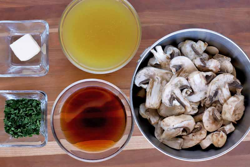 Overhead shot of two square glass bowls of butter and minced parsley, two round glass bowls of marsala wine and chicken broth, and a small stainless steel bowl of sliced crimini muchrooms, on a wood surface.