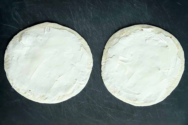 Overhead horizontal image of two flour tortillas spread with a thin layer of cream cheese, on a gray scratched surface.