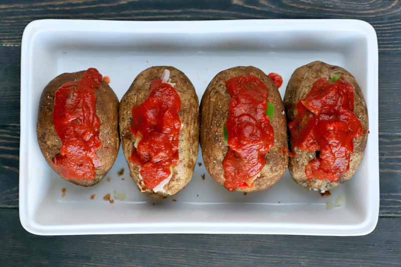 Overhead shot of four baked potatoes arranged in a row in a white, rectangular, ceramic baking dish, filled with vegetables and topped with marinara sauce, on a dark brown wood surface.