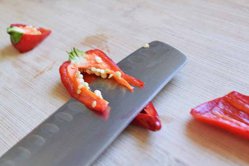 Closeup image of a knife slicing a red chili pepper to remove the seeds and pith inside, on a blonde unfinished wood cutting board.