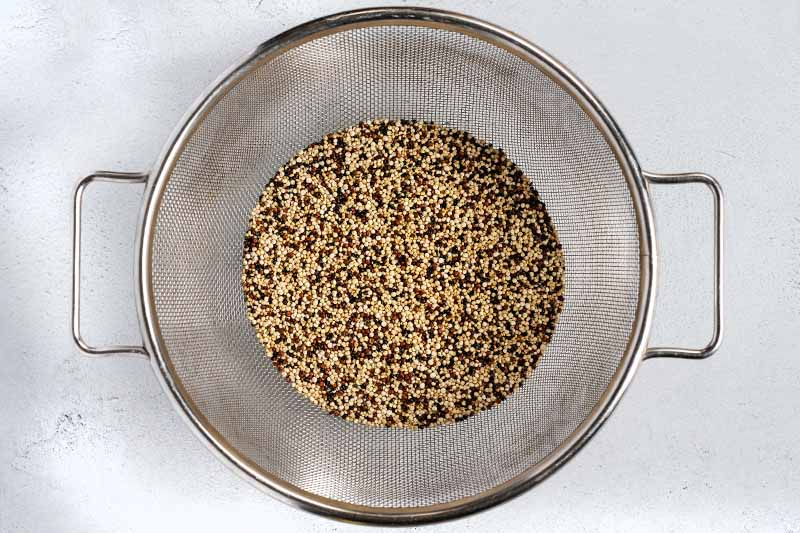 Overhead shot of a metal fine mesh strainer with handles, with uncooked multicolored quinoa at the bottom, on a white background with gray speckles.